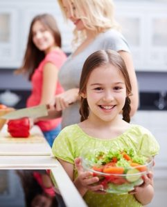 Portrait of happy girl with vegetable salad on background of her